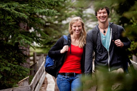 A man and woman on a hike in the forest, smiling at the camera Stock Photo - 7682994