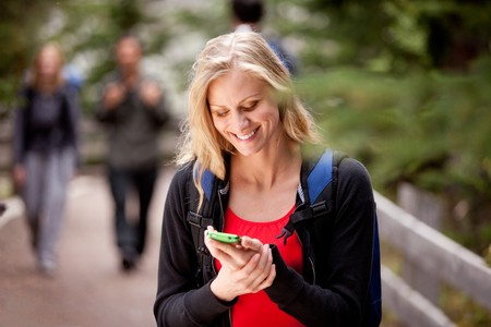 phone message: A young woman reading a friendly text while outdoors