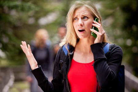 A woman talking on the phone, frustrated with the person she is talking to photo