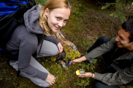 treasure hunt: A young man and woman finding a geocache hidden in the forest Stock Photo
