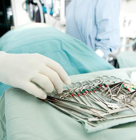 quirurgico: Disparo de detalle de los instrumentos de cirug�a steralized con una mano agarrando una herramienta  Foto de archivo
