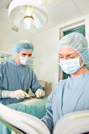 malpractice: A surgeon unsure of the operation following a manual Stock Photo