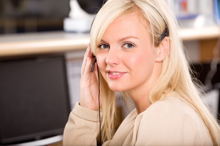 A happy friendly receptionist using a headset photo