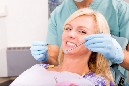 dental hygienist: A smiling woman at the dentist ready for a check-up Stock Photo