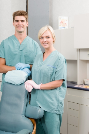 A happy dentist and assistant standing in a dental clinic photo