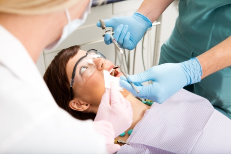 oral surgery: A dentist giving a freezing needle to a worried patient Stock Photo
