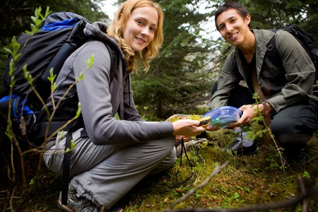 caching: Two people finding a geocache in the forest.  Shallow depth of field with sharp focus on woman. Stock Photo
