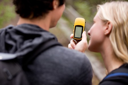 A couple outdoors in the forest using a GPS.  Sharp focus on the GPS device. photo