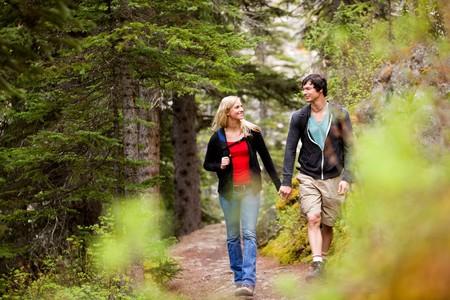 caminando: Una feliz pareja mirando atmosfera y caminar en el bosque de mano  Foto de archivo