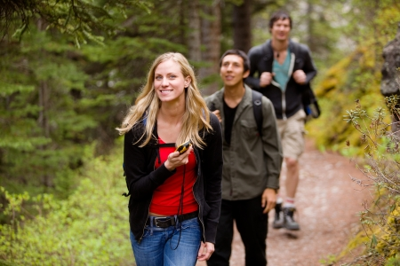 hike: A woman using a GPS in the forest on a camping hike Stock Photo