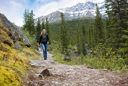 Eine glückliche Frau zu Fuß auf ein Pfad auf einem Berg-Wanderung im Banff Nationalpark
