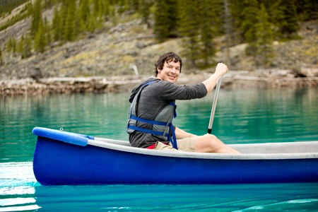 A portrait of a smiling man in a canoe on a glacial lake photo