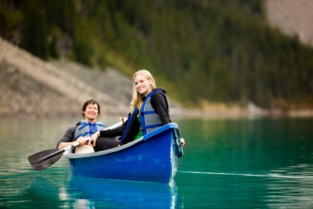 A portrait of a happy woman on a canoeing trip with a man Stock Photo