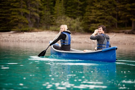 A man and woman paddling in a canoe on a lake photo