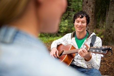 A man playing a guitar and singing for a woman Stock Photo - 8043936