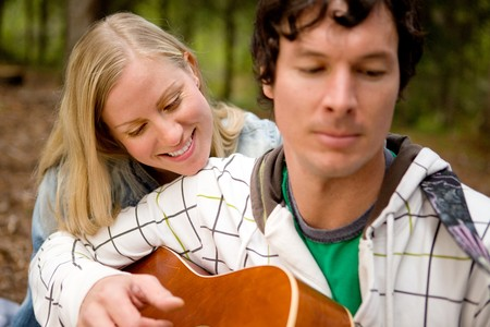 A couple enjoying themselves outdoors with a guitar, focus on woman photo