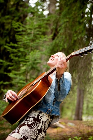 A woman singing freely in the forest with a guitar - sharp focus on guitar  Stock Photo