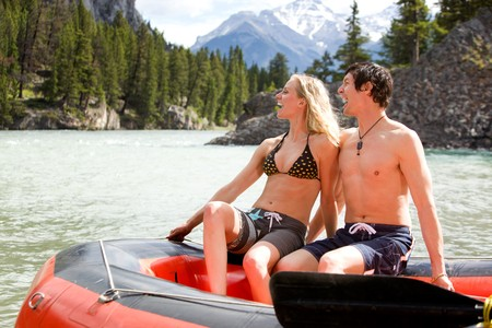 A man and woman rafting on a river photo