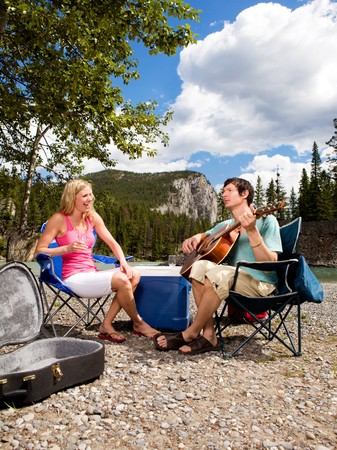 A happy couple with a guitar outdoors having fun photo