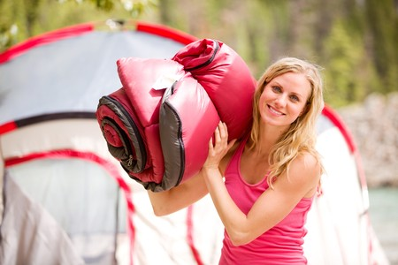 A portrait of a woman holding a sleeping bag Stock Photo
