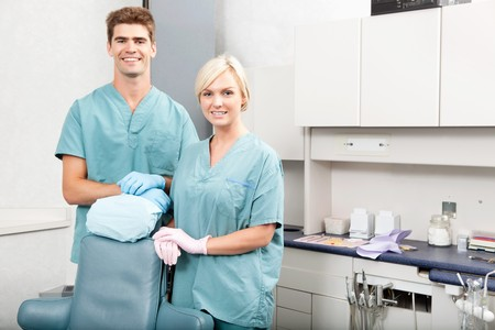 dental assistant: Portrait of a confident male and female dentists smiling at dental clinic Stock Photo