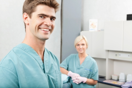 Portrait of male dentist with female assistant standing at dental clinic photo