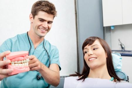 explaining: Male dentist explaining a female patient denture work in dental clinic