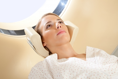 A young woman with eyes open preparing for a CT scan photo