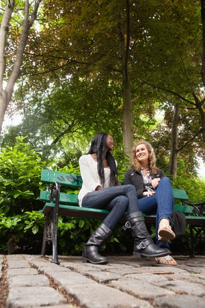 2 pessoas: Low angle view of two young relaxed female friends chatting in the park Imagens