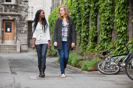 two people talking: Two young friends having a casual chat while walking on street Stock Photo