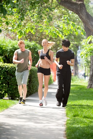 Three friends jogging in the park against blur background photo