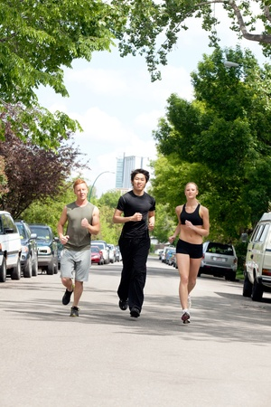 Friends jogging on the street by land vehicle photo