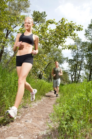 Young man and woman running on a pathway photo