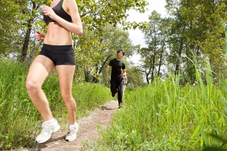 Friends in fitness clothing running on pathway Stock Photo - 9283521