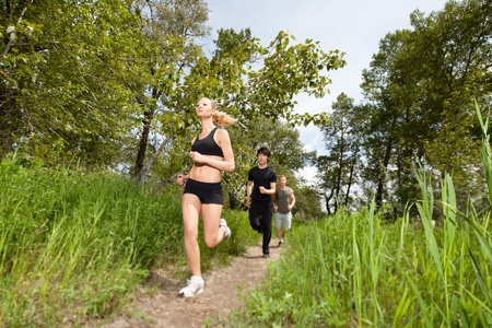 Health conscious people running on forest trail photo