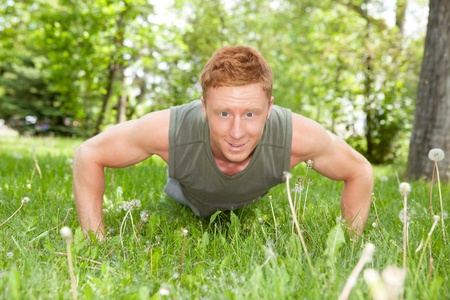 An attractive Caucasian man doing a push up outdoors Stock Photo - 9283427