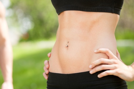 Sexy and fit belly on young woman against blur background photo