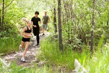 Three friends running in the forest on pathway photo