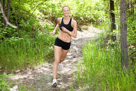 athleticism: Portrait of beautiful young woman running in the forest