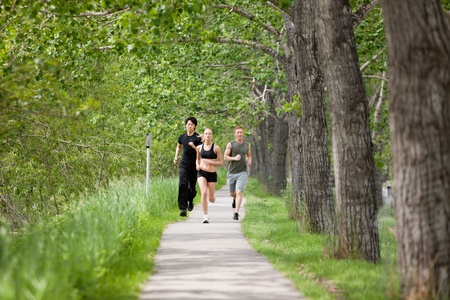 Young people running on walkway by trees photo