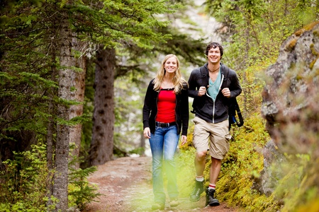 A happy man and woman hiking on a camping trip photo