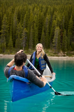 A happy couple canoeing on a glacial lake photo