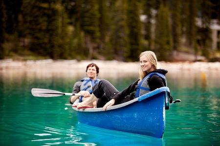 louise: A happy couple relaxing in a canoe on a glacial lake Stock Photo