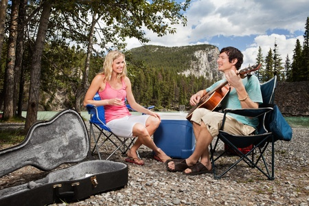 Young woman listening to man playing guitar in forest photo