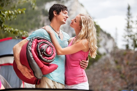 Young woman carrying sleeping bag and embracing woman while camping photo