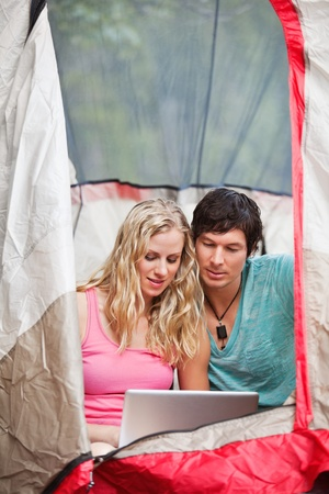 Young couple using laptop in tent while camping photo