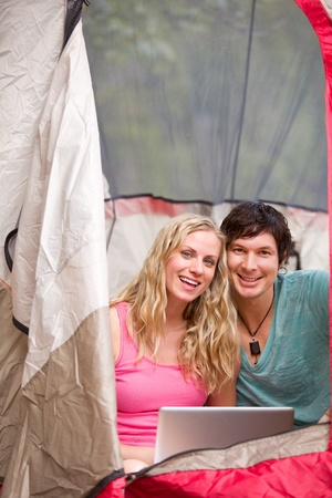 A portrait of a happy camping couple with a laptop, smiling at the camera photo