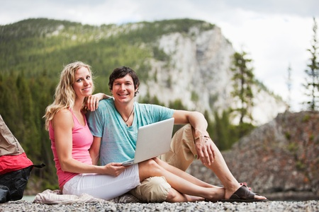 Portrait of happy relaxed young couple with laptop while camping photo