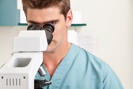 Closeup of young male doctor viewing through microscope photo