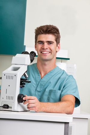 Portrait of happy male doctor with microscope photo